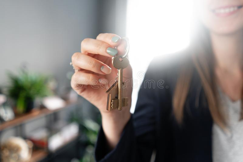House key rotates on the finger in womans hands. Young pretty woman smiles. Modern light lobby interior. Real estate stock image
