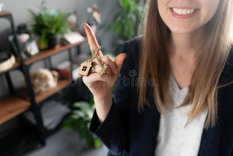House key rotates on the finger in womans hands. Young pretty woman smiles. Modern light lobby interior. Real estate stock photo