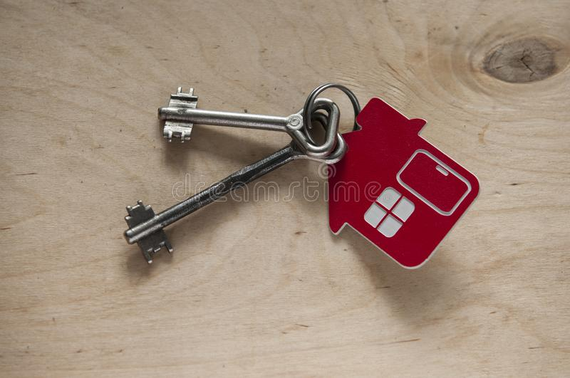 House key on a house shaped keychain on wooden background. Real estate concept. Two old metal keys with symbol of a family house on the wooden background stock photos