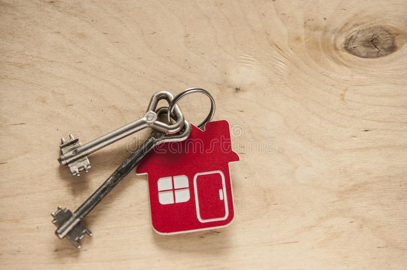 House key on a house shaped keychain on wooden background. Real estate concept. Two old metal keys with symbol of a family house on the wooden background royalty free stock images