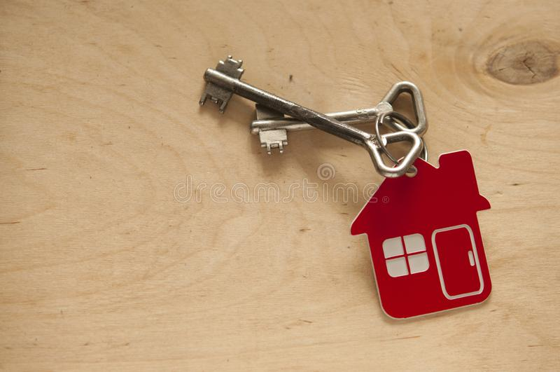 House key on a house shaped keychain on wooden background. Real estate concept. Two old metal keys with symbol of a family house on the wooden background stock photo