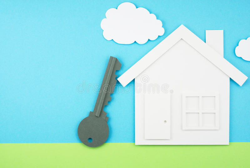 House and key shaped paper cutout on sky and grass field made of royalty free stock images