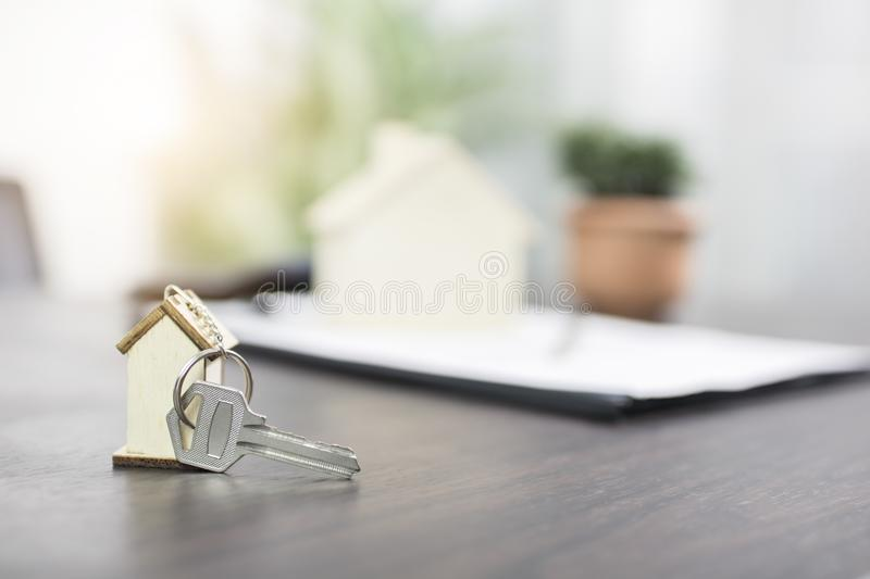 House key on table with contract form, selling and buying home o. R condo concept royalty free stock image