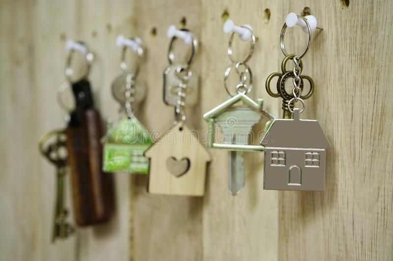 House key with wooden home keyring hanging on wood board background, property concept, copy space. House key with wooden home keyring hanging on wood board royalty free stock images