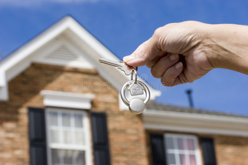 House keys. Woman holding a key for a house on a keychain in front of a brick house royalty free stock photography