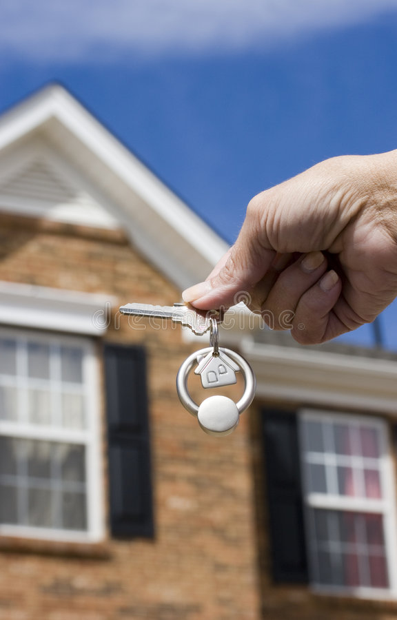 House keys. Woman holding a key for a house on a keychain in front of a brick house stock photos
