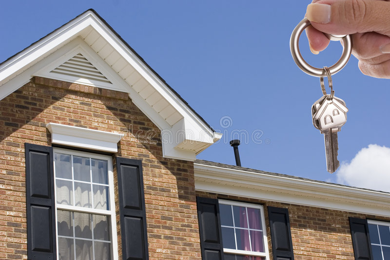 House keys. Woman holding a key for a house on a keychain in front of a brick house stock images