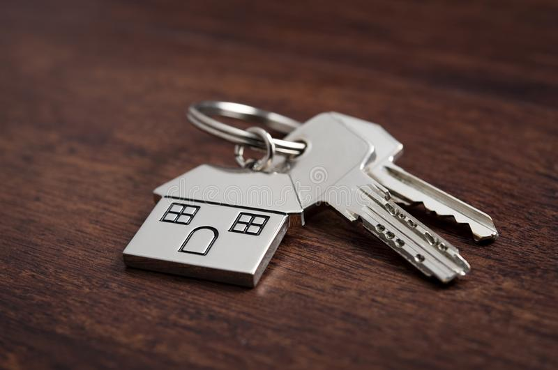 House keys. Close up of house keys on a house shaped keychain on wooden background. Concept for real estate, moving home or renting property on dark wood stock images