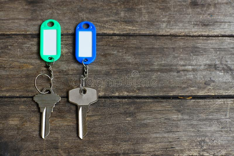 House keys with color tag keyring with green garden background, property concept, copy space stock photo
