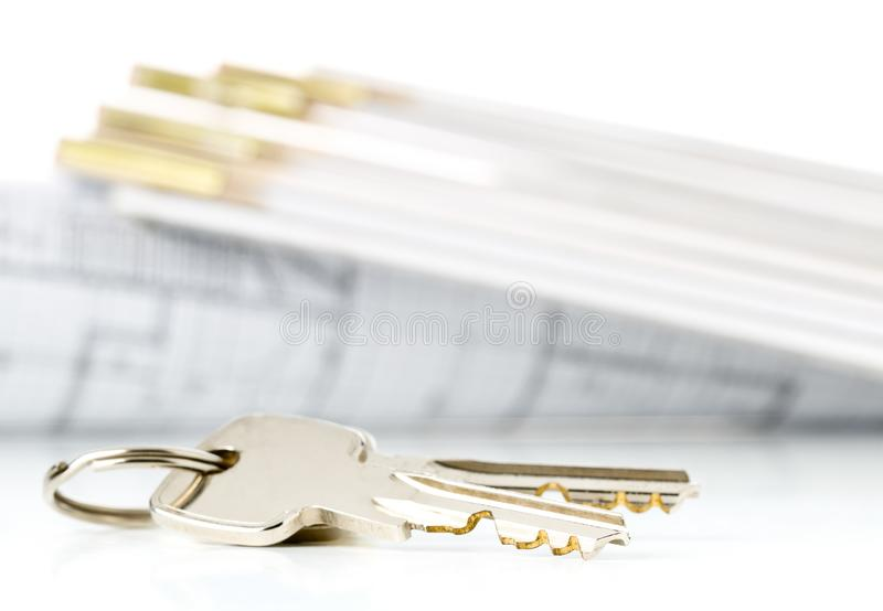 House keys in front of house architectural blueprint and folding rule over white background - home owner, real estate or house. House keys in front of house royalty free stock photo