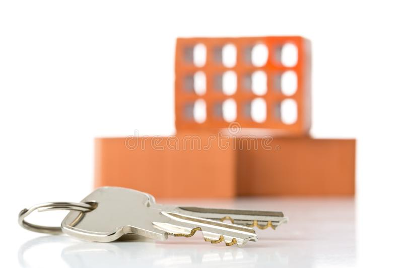House keys in front of bricks over white background - home owner, real estate or house building concept. House keys in front of bricks over white background with stock photo