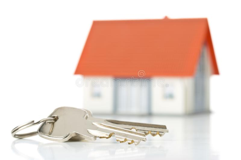House keys in front of model house over white background - home owner, real estate or house building concept. House keys in front of model house over white royalty free stock images