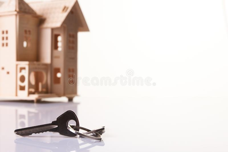 House and house keys isolated on white background. With copy space. Mortgage, investment, real estate and property concept - close up of key and home model stock photos