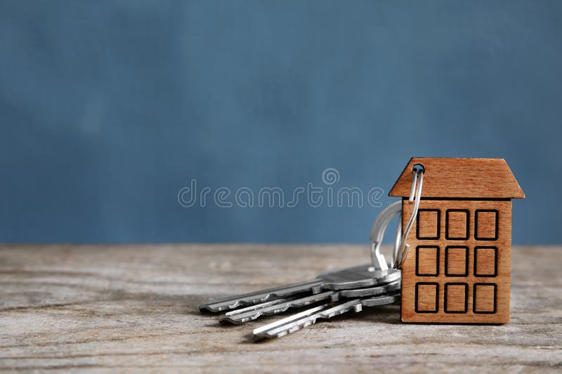 House Keys With Trinket On Wooden Table Against Color ...