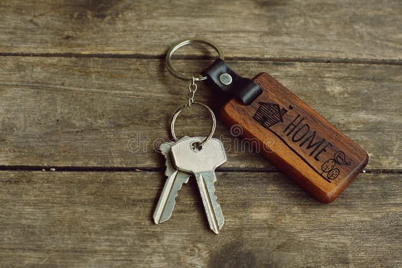 House keys with wooden home keying on wood table, copy space, property concept royalty free stock photo