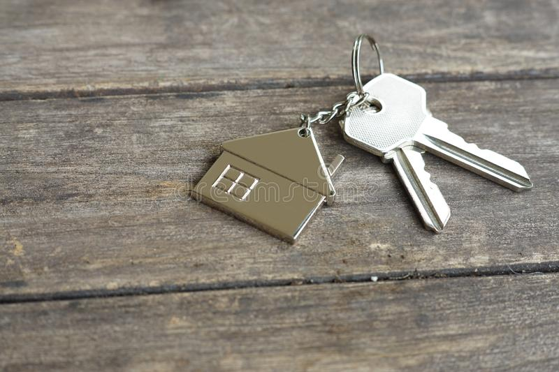 House keys with wooden home keying on wood table, copy space, property concept royalty free stock images
