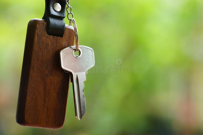 House keys with wooden home keyring with green garden background, property concept, copy space royalty free stock image