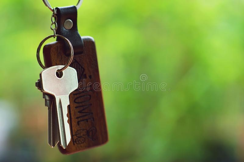 House keys with wooden home keyring with green garden background, property concept, copy space royalty free stock photo
