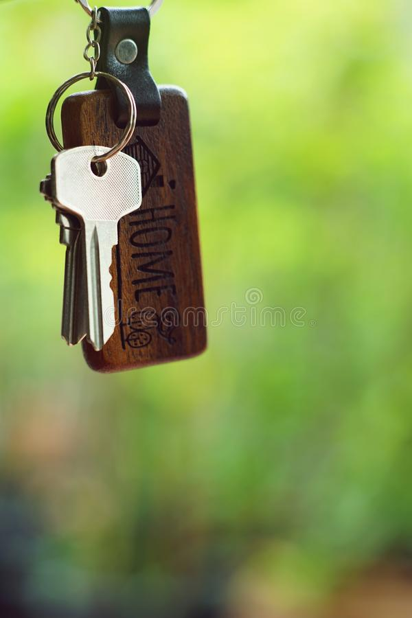 House keys with wooden home keyring with green garden background, property concept, copy space stock image