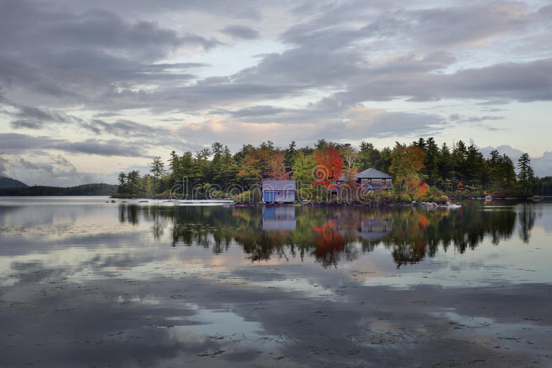 House and lake reflection. Near Lake Squam in New Hampshire in early Autumn stock photo