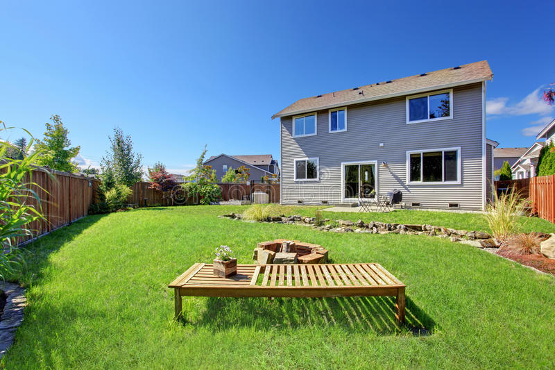 House with large backyard and patio area. Backyard patio area with wooden bench and fire pit royalty free stock photos