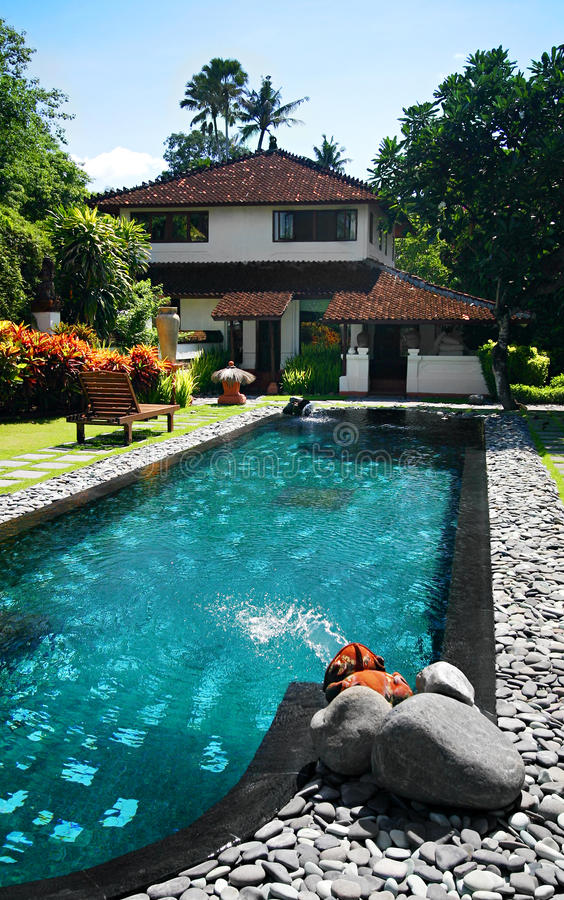 House with large outdoor swimming pool. A photograph of a large mansion house with a blue turquoise swimming pool in the front yard, with colorful tropical stock photography