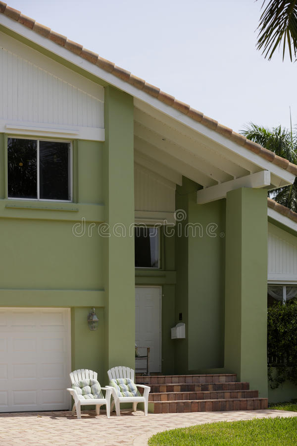House with lawn chairs. Stock image of a green painted house with lawn chairs stock photos