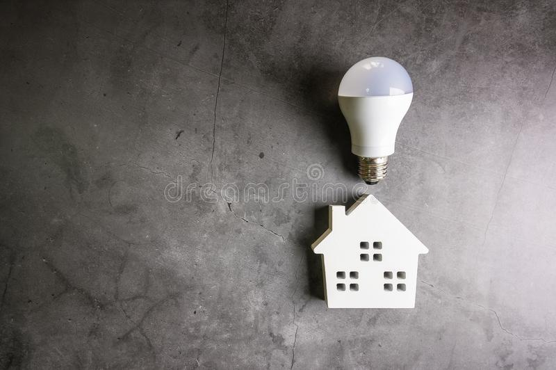House and light bulbs on stone pattern background with copy space.Home Repair concept, Repair maintenance concept, Renovation royalty free stock image