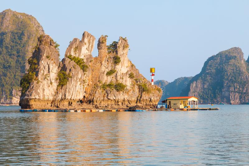 Vietnam, Ha Long Bay landscape with camel rock. House on the living platform next to the limestone rock looking like a camel with two back humps in Ha Long Bay stock photography