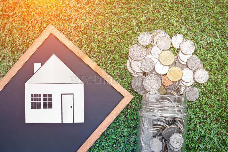 House loan business concept with coin fall from glass jar and ho royalty free stock photo