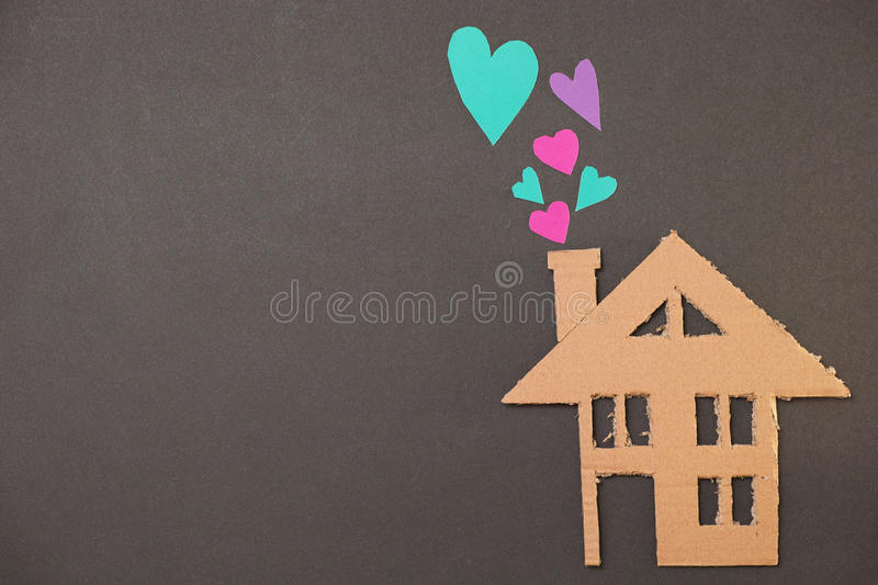 House of love. Building cut out of pasteboard with paper hearts coming out of its chimney for your construction, architecture and love concepts - copy space to royalty free stock photography