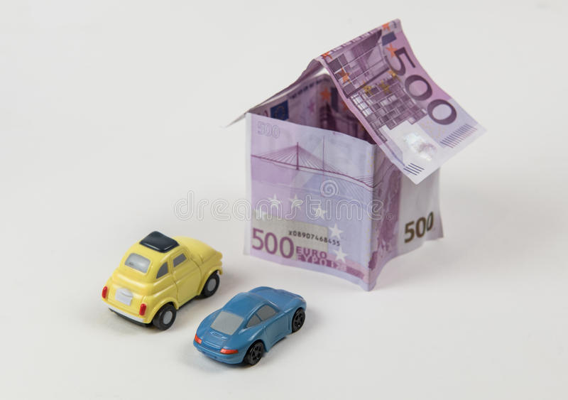 House made with 500 euro banknotes. And cars parked outside isolated on a white background stock photo
