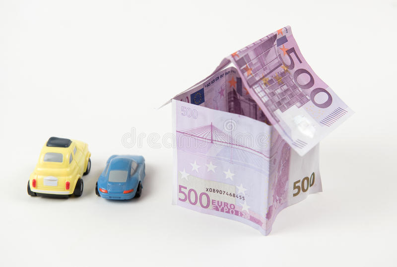 House made with 500 euro banknotes. And cars parked outside on a white background stock photo
