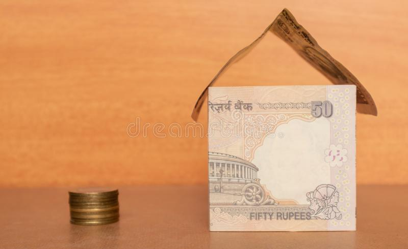 House made from the Indian currency with Coins stock photo