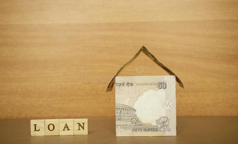 House made from the Indian currency notes and Home Loan in wooden block letters on wooden background royalty free stock photos