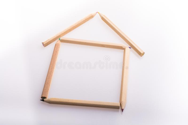 A house made of pencils on white background. A house made of pencils on a white background stock images