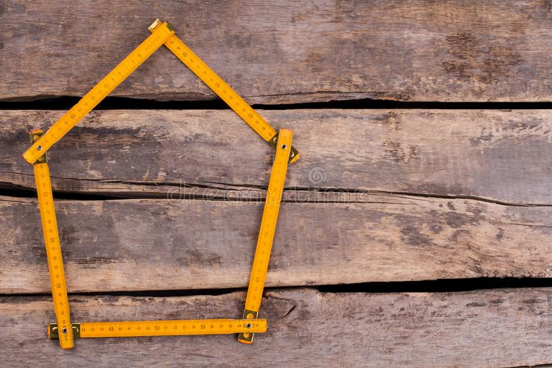House made from yellow folding ruler. Yellow folding ruler in a shape of house. Space for text. Home renovation concept royalty free stock image