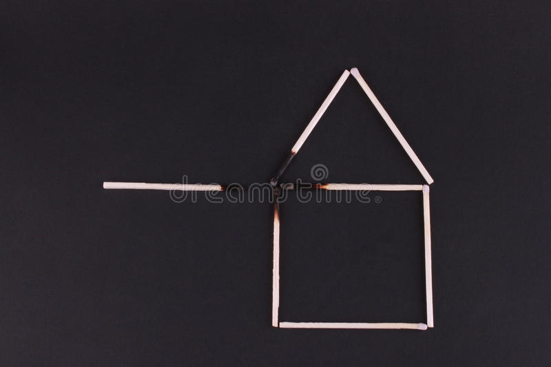 House of matches. House made from matches burned on a black background stock image