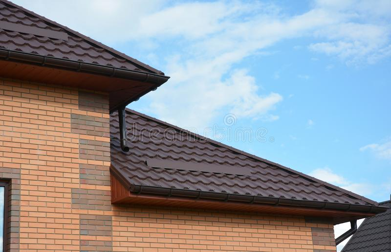 House metal roof corner with rain gutter pipeline. Guttering royalty free stock image