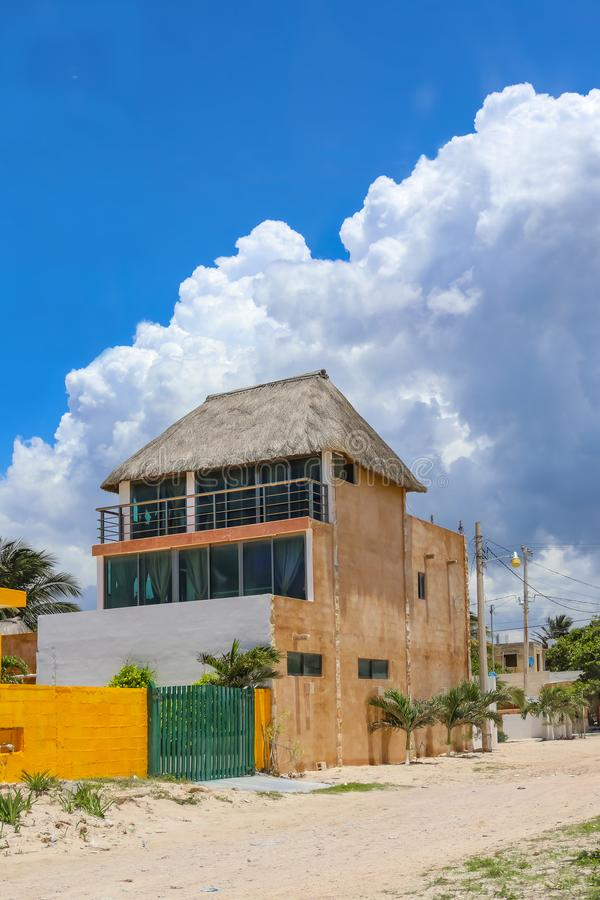 House in Mexican village built tall for ocean view over the roofs of other buildings on the beach with thatch roof against very bl stock photos