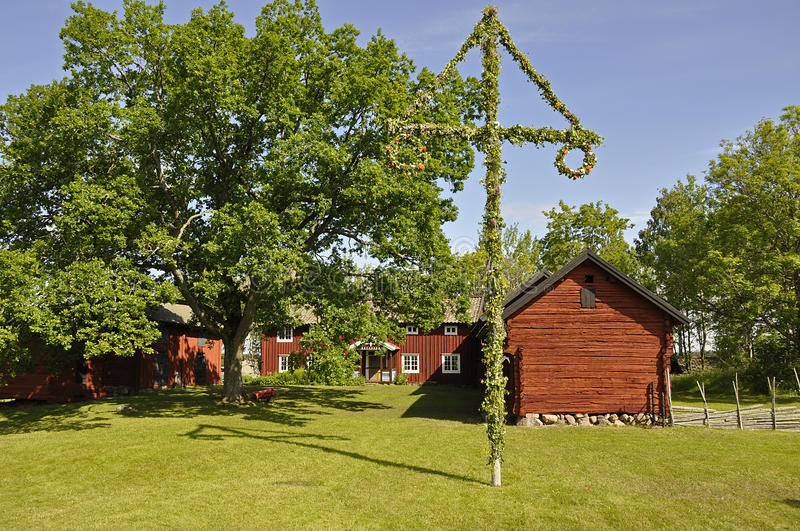 House and midsummer tree. A view of an old red house in Sweden and a midsummer tree decorated with traditional greenery on the lawn in the foreground royalty free stock images