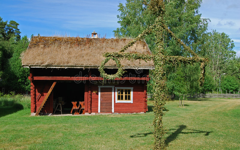 House and midsummer tree. A view of an old red house in Sweden and a midsummer tree decorated with traditional greenery on the lawn in the foreground royalty free stock photography