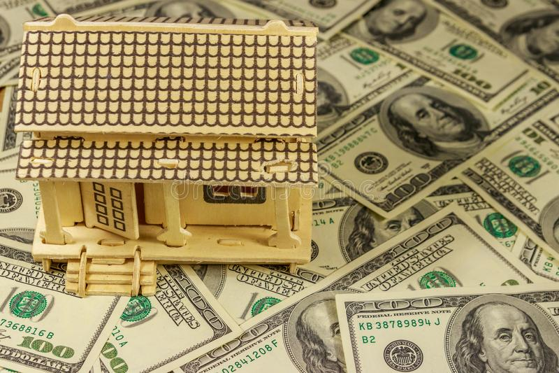 House model on background of U.S. one hundred dollar bills. Property investment, home loan, house mortgage, real estate concept stock images