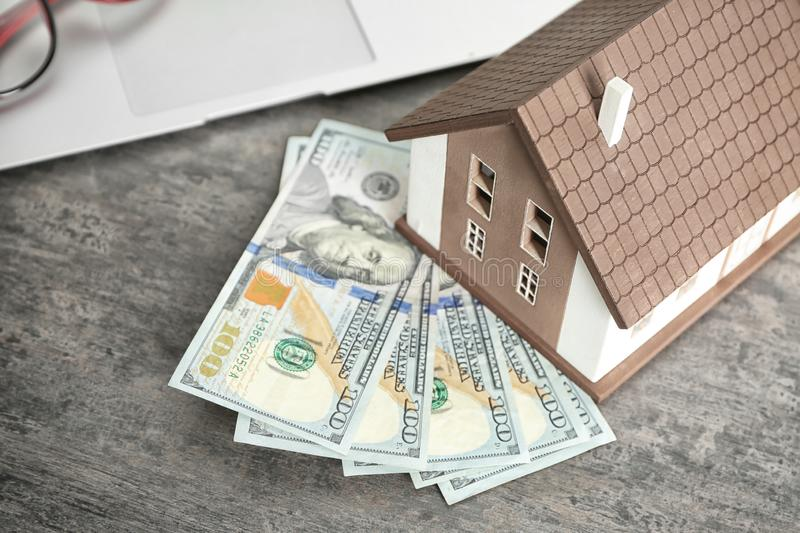 House model and banknotes on grey table, closeup. Mortgage concept stock photography