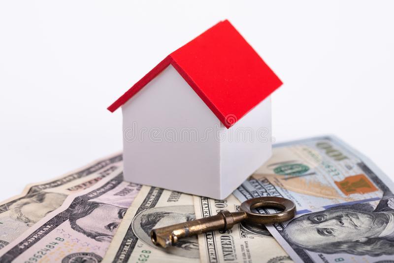 House Model With Banknotes And Key. Close-up Of House Model With Banknotes And Key On White Background stock image