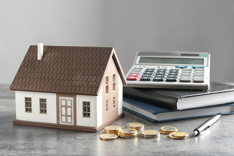 House model, calculator and coins on grey table. Mortgage concept stock images