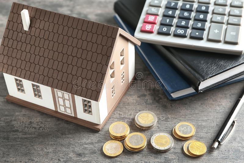 House model, calculator and coins on grey table. Mortgage concept royalty free stock photography