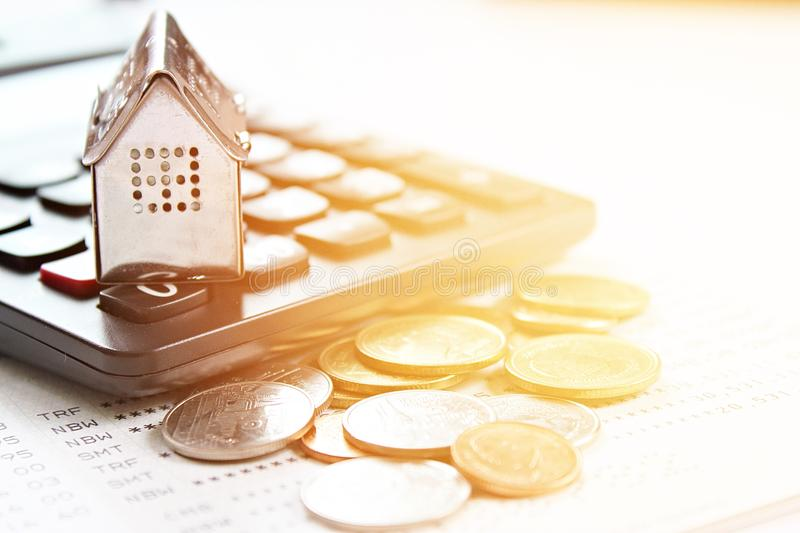 House model, calculator and coins on office desk table. Business, finance, saving money, property ladder or mortgage loan concept : House model, calculator and royalty free stock photography