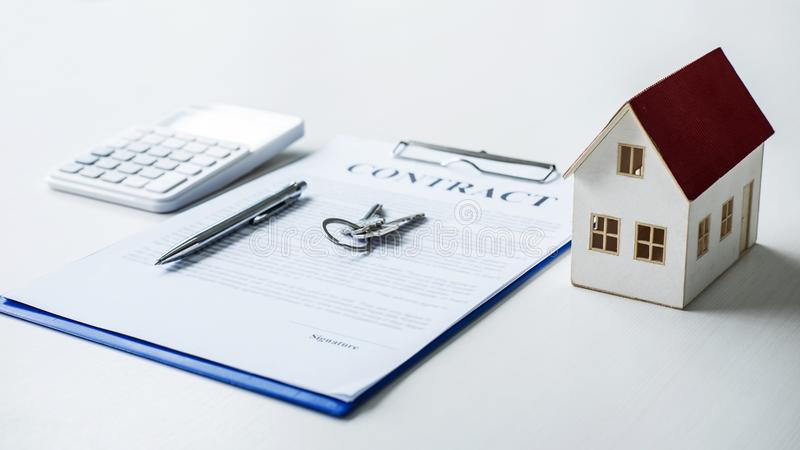 House model, calculator and house key lying on real estate contract, home loan and investment concept.  stock image