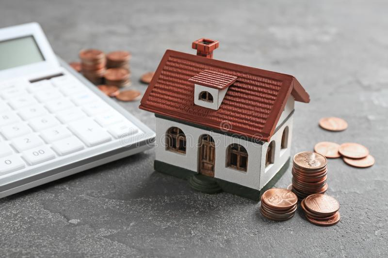 House model, coins and calculator. On grey background stock image